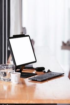 Mockup leeg scherm tablet met toetsenbord op houten aanrechttafel in café, verticale weergave.