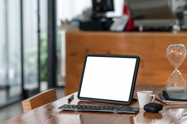 Mockup leeg scherm tablet met toetsenbord op houten tafel in café kamer.