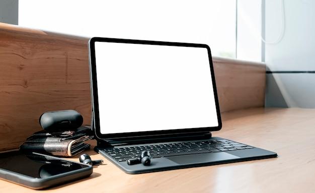Mockup leeg scherm tablet met toetsenbord op houten teller tafel in café