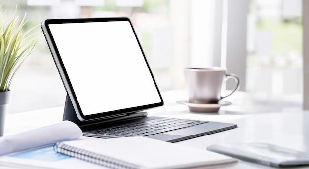 Mockup leeg scherm tablet met toetsenbord op tafel in moderne kamer.