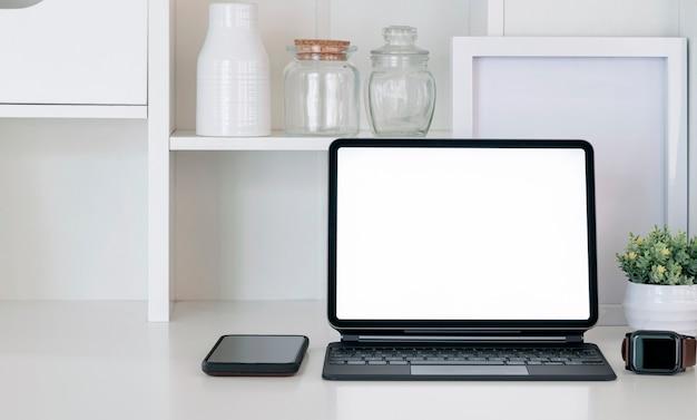 Mockup leeg scherm tablet met toetsenbord, smartphone en smartwatch op witte tafel.