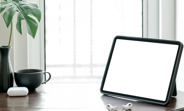 Mockup leeg scherm tablet op houten tafel bij het raam in de woonkamer met kopie ruimte.