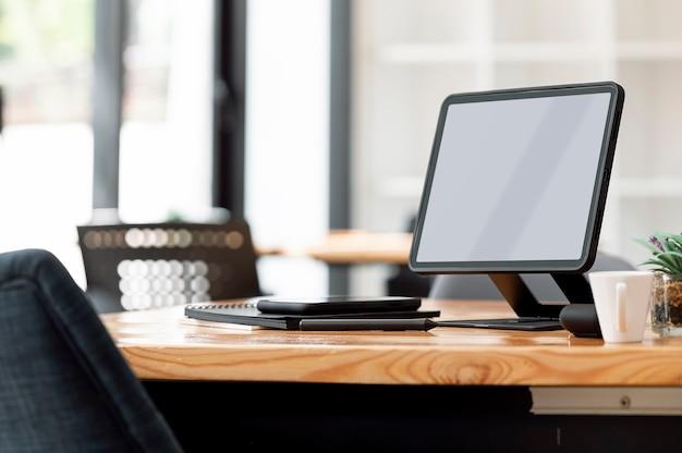 Mockup leeg scherm tablet op standaard en gadget op houten tafel in co-werkruimte.