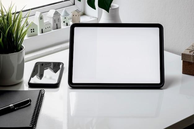 Mockup leeg scherm tablet, smartphone en notebook op witte tafel.