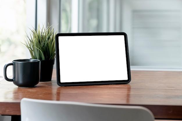 Mockup leeg scherm tablet, zwarte koffiekopje en kamerplant op houten tafel in de woonkamer met kopieerruimte.