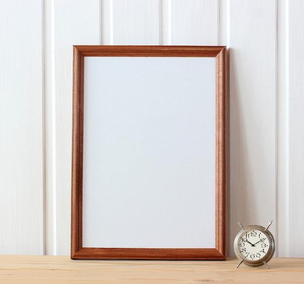 Mockup, maker van scènes. leeg houten frame en retro wekker op tafel. kopieer ruimte.