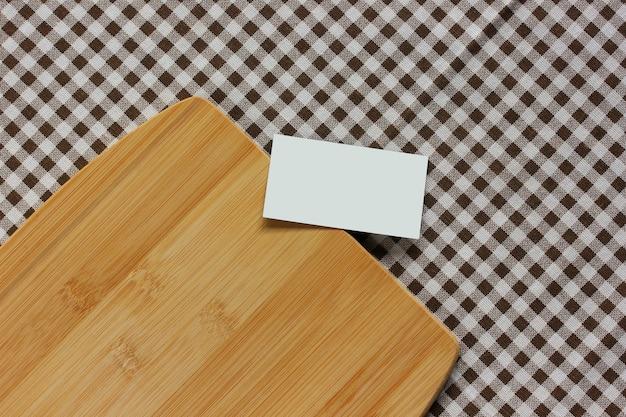 Mockup, maker van scènes. lege visitekaartje en bamboe snijplank op een geruit tafelkleed, bovenaanzicht. keukentafel. kopieer ruimte.