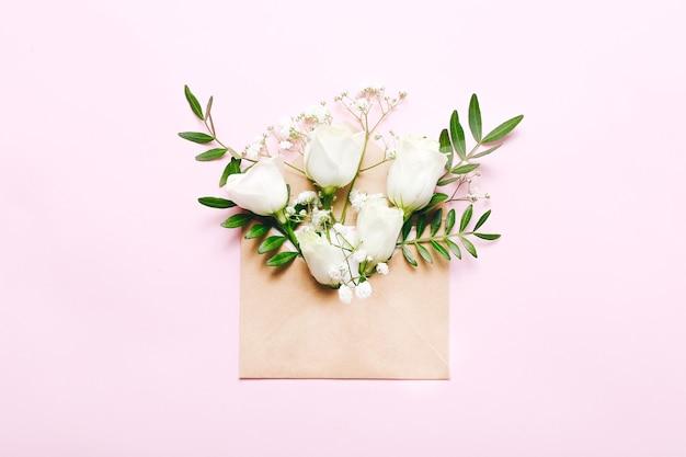 Mockup met ambachtelijke envelop en bloemen op roze.