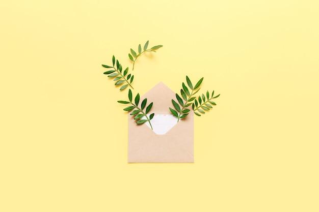 Mockup met ambachtelijke envelop en groene bladeren op geel.