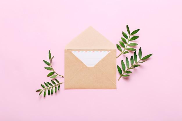 Mockup met ambachtelijke envelop en groene bladeren op roze.