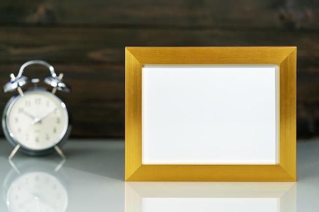 Mockup met gouden frame en wekker
