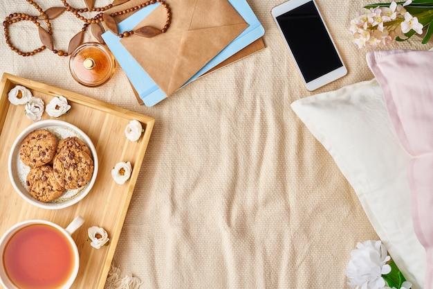 Mockup met vrouwentoebehoren op bedthee, koekjes, hoofdkussens, bloemen, brief, notitieboekje