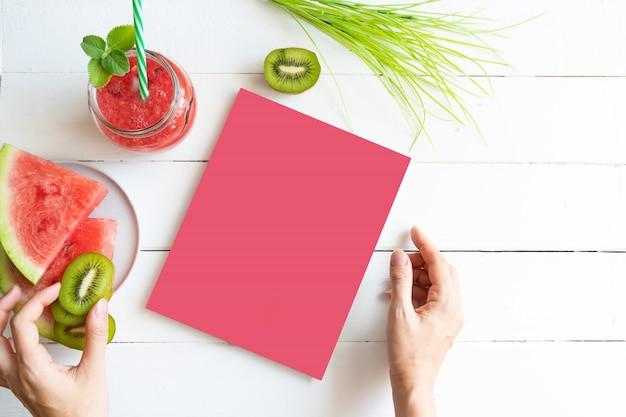 Mockup over gezonde voeding. watermeloen smoothie, plakjes kiwi en watermeloen op tafel. meisje houdt een boek in haar handen kopieer ruimte