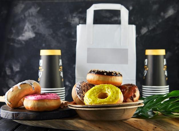 Mockup-pakket voor levering van veelkleurige donuts met glazuur en besprenkeling, wegwerpkoffiekopjes. levering van voedsel en natuurlijke ingrediënten, afvalvrije productie.