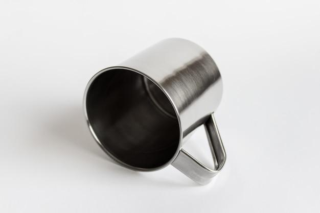 Mockup-sjabloon van enkele zilveren glanzende metalen roestvrijstalen mok die op een witte ondergrond ligt.
