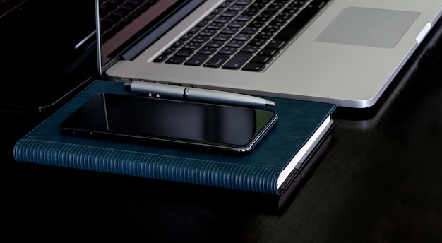 Mockup smartphone op notebook en laptopcomputer op zwarte boven tafel.