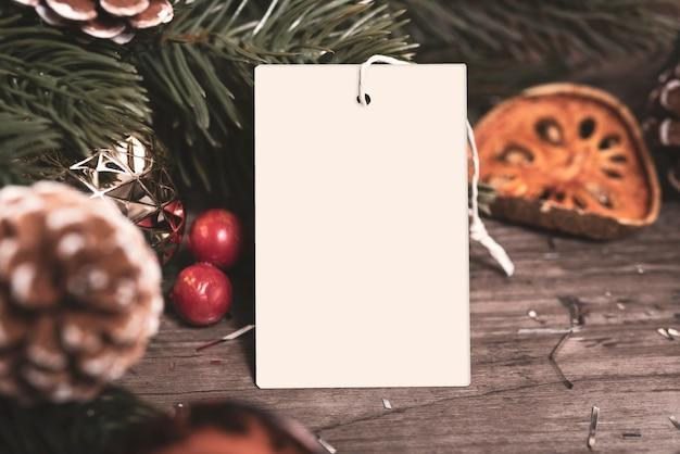 Mockup tag papieren kaart met dennenappels kerstdecoratie op houten tafel achtergrond.