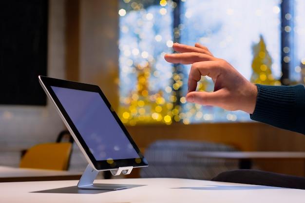 Mockup-technologie. zakenman toont ok op de achtergrond van een digitale tablet met wit scherm.