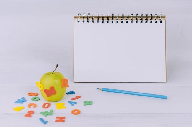 Mockup terug naar school. groene appel met gekleurde letters en blocnote ruimte.