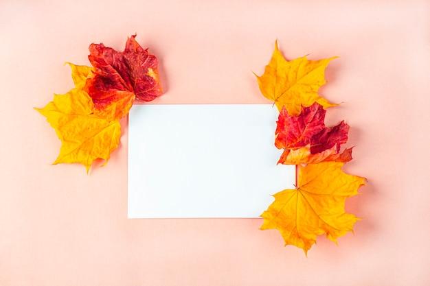 Mockup uitnodigingskaart. sjabloon leeg wenskaart voor de bruiloft, verjaardag en andere evenementen. papier op perzik kleur achtergrond met droge herfstbladeren.