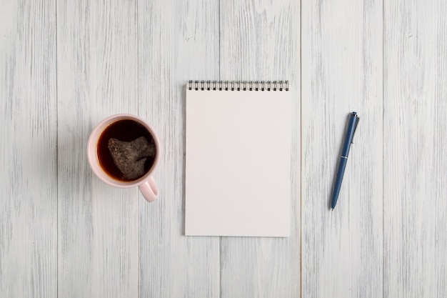 Mockup van een blanco notitieblok, een kopje koffie en een automatische balpen