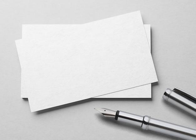 Mockup van één visitekaartje met vulpen bij witte geweven document achtergrond