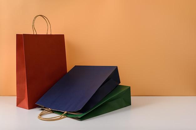 Mockup van lege ambachtelijke pakket of kleurrijke papieren boodschappentas met handvatten
