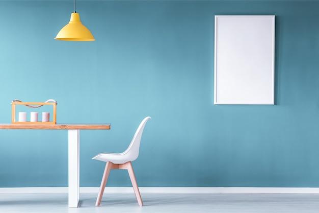 Mockup van poster in blauw eetkamerinterieur met gele lamp boven houten tafel naast wit