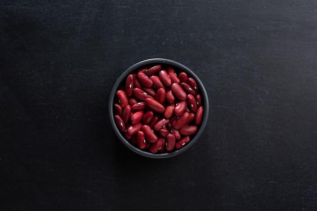 Mockup van rode bonen in kleine kom op donkere achtergrond.