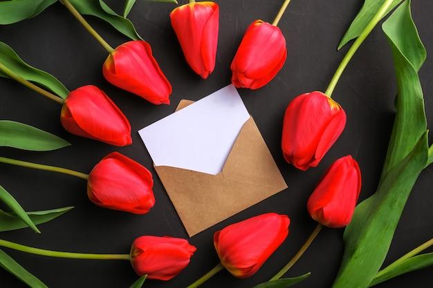 Mockup van vers rood tulpenboeket en witte lege groetkaart in kraftpapier-envelop
