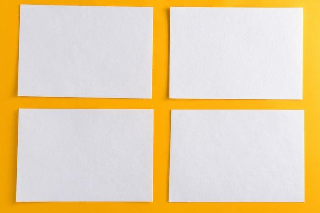 Mockup van vier witte visitekaartjes op gele design papier achtergrond