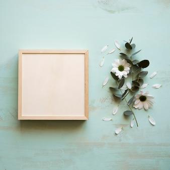 Mockup van vierkante frame naast bloem