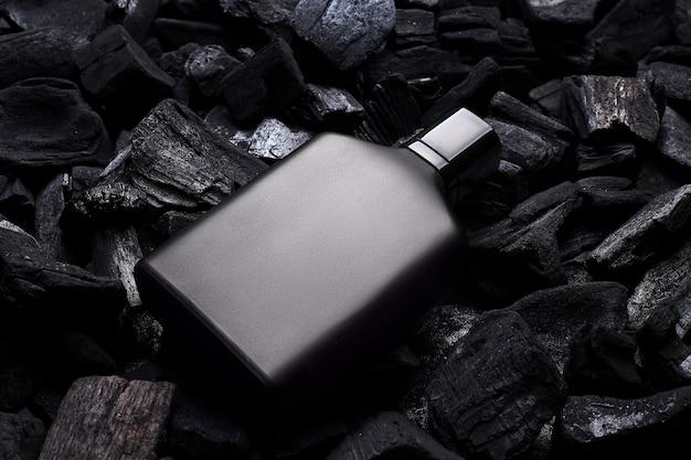 Mockup van zwarte geur parfumfles mockup op donkere kolen achtergrond. bovenaanzicht. horizontaal