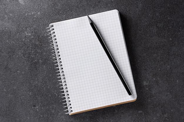 Mockup voor notebooks. a5-papier met zwart potlood op zwart. bovenaanzicht.