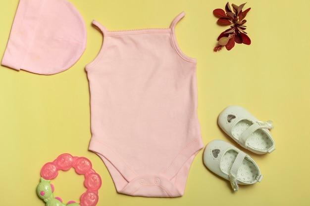 Mockup voor ontwerp en plaatsing van logo's, reclame. roze baby romper, bovenaanzicht, mock up op gele achtergrond.