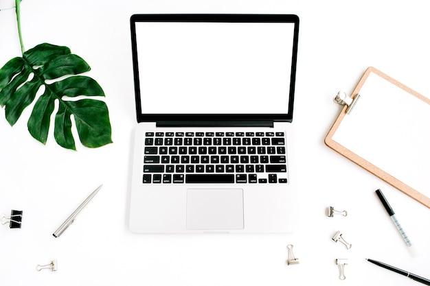 Mockup voor thuiskantoor. laptop met leeg scherm, klembord, palmblad en accessoires