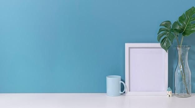 Mockup wit houten frame met mok en vaas met plant op witte bovenste tafel en lichtblauwe muur