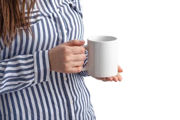 Mockup witte koffiekop of mok in vrouwelijke handen op wit