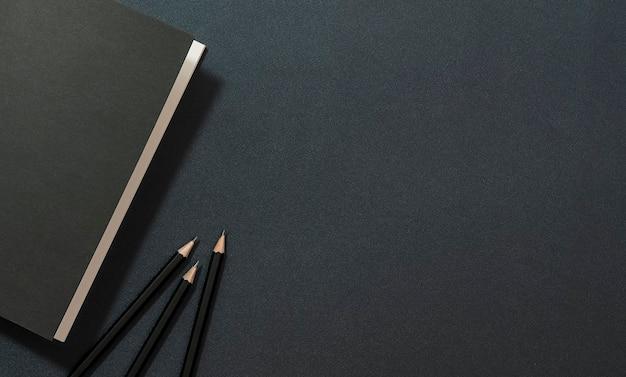 Mockup zwart boek en potlood op zwart leer