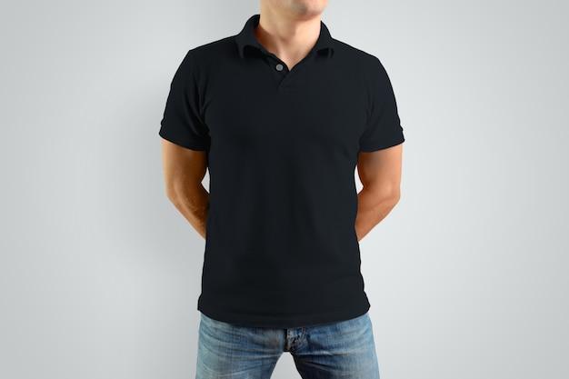 Mockup zwart poloshirt op een sterke man met zijn handen achter zijn rug. geïsoleerd op een grijze achtergrond. sjabloon kan worden gebruikt voor uw ontwerp.