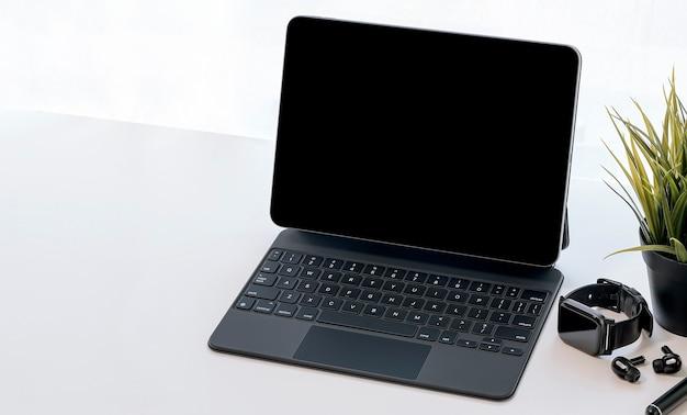 Mockup zwart scherm tablet met magisch toetsenbord, smartwatch en oortelefoon op witte bovenste tafel