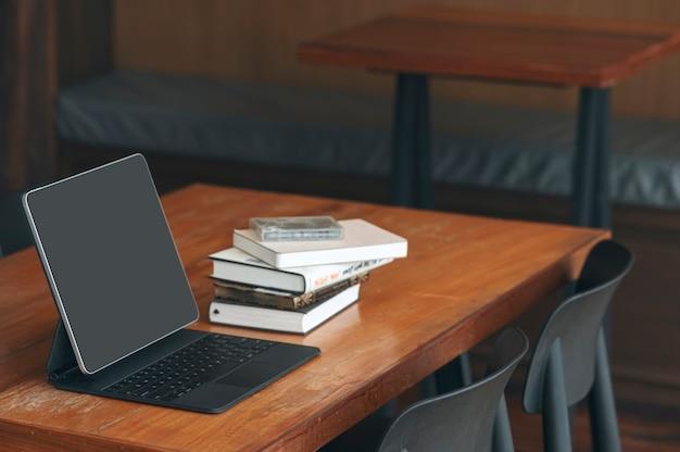Mockup zwart scherm tablet met toetsenbord op oude houten tafel in donkere toon kantoorruimte.