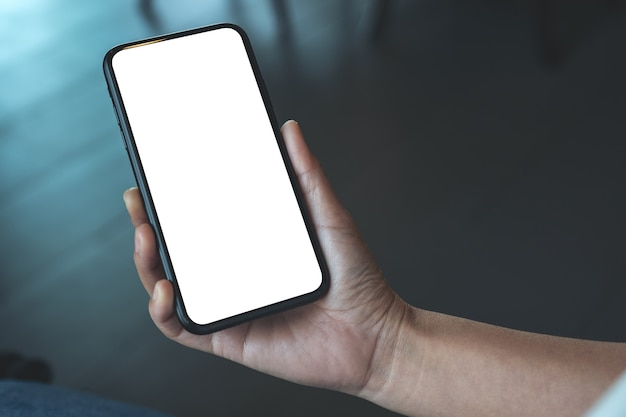Mockupafbeelding van de hand van een vrouw met zwarte mobiele telefoon met een leeg bureaublad