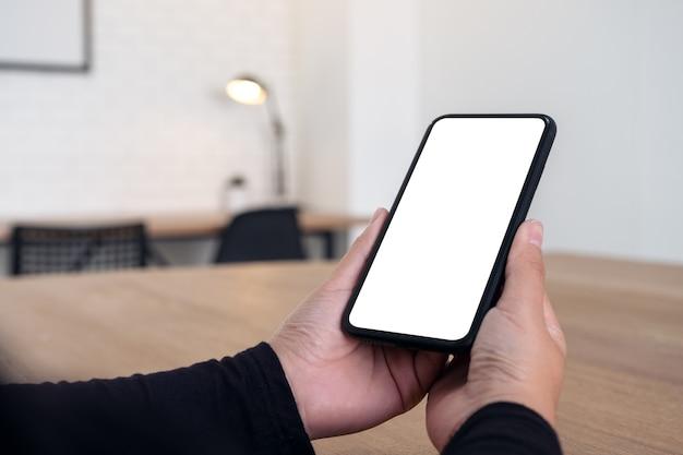 Mockupafbeelding van handen met zwarte mobiele telefoon met leeg wit bureaublad op houten tafel