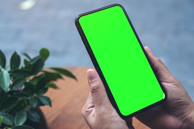 Mockupafbeelding van handen met zwarte mobiele telefoon met leeg wit bureaublad