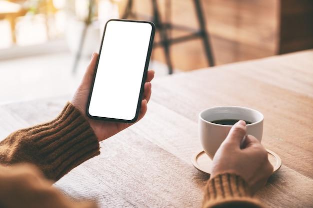 Mockupbeeld van de hand van de vrouw die zwarte mobiele telefoon met leeg scherm vasthoudt terwijl ze koffie drinkt