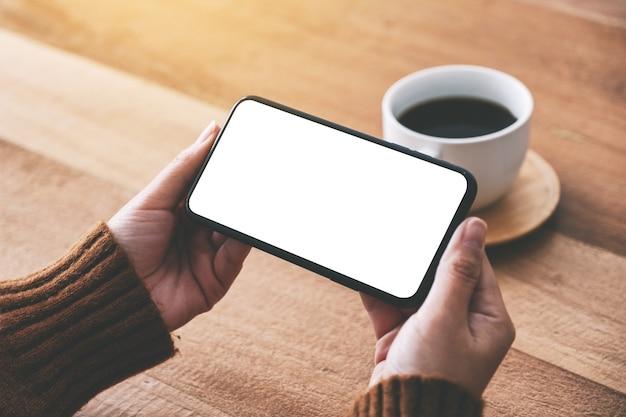 Mockupbeeld van de hand van de vrouw met zwarte mobiele telefoon met leeg scherm horizontaal met koffiekopje op houten tafel