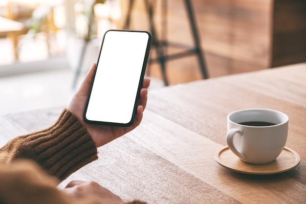 Mockupbeeld van de hand van de vrouw met zwarte mobiele telefoon met leeg scherm met koffiekopje op houten tafel