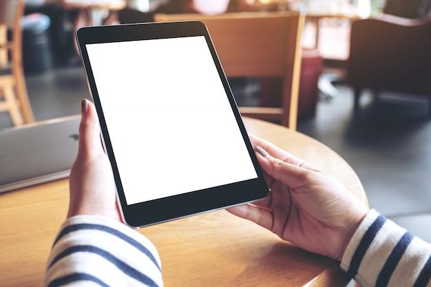 Mockupbeeld van de handen van de vrouw die zwarte tabletpc met het lege witte desktopscherm in koffie houden