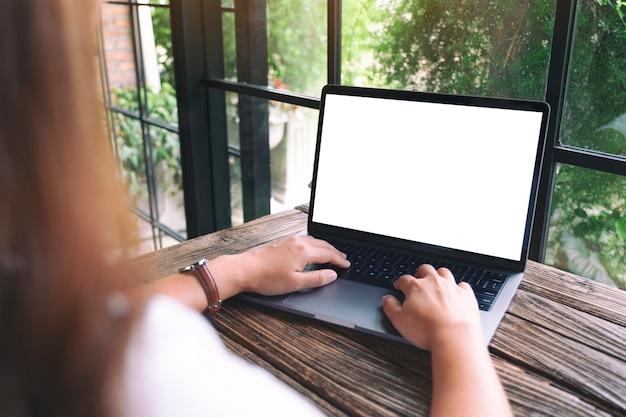 Mockupbeeld van een vrouw die op laptoptoetsenbord gebruikt en typt met een leeg wit desktopscherm op houten tafel